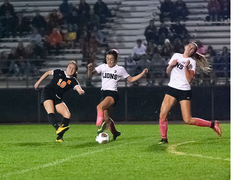 PHOTO COURTESY: MICHELLE MOLLENHOUR - Scappoose Indians junior midfielder Taryn Verzino (left) tries to get the ball past St. Helens Lions defenders Amanda Nichols (3) and Mackenzie Carlson during a league game Tuesday at Scappoose. The Indians won, 4-0.