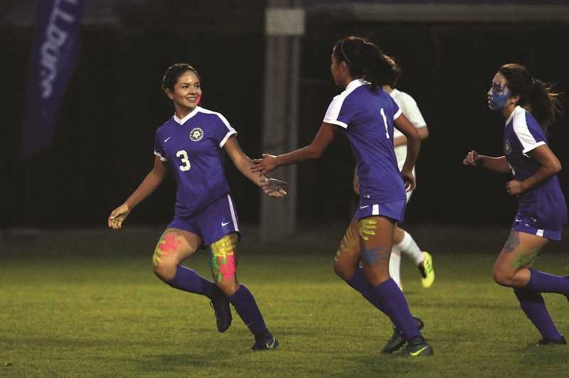 PHIL HAWKINS - Woodburn sophomore Yahaira Rodriguez (left) congratulates freshman teammate Myranda Marquez, who scored the opening goal in the first half of the Bulldogs' 2-0 win over No. 7 Philomath on Tuesday.