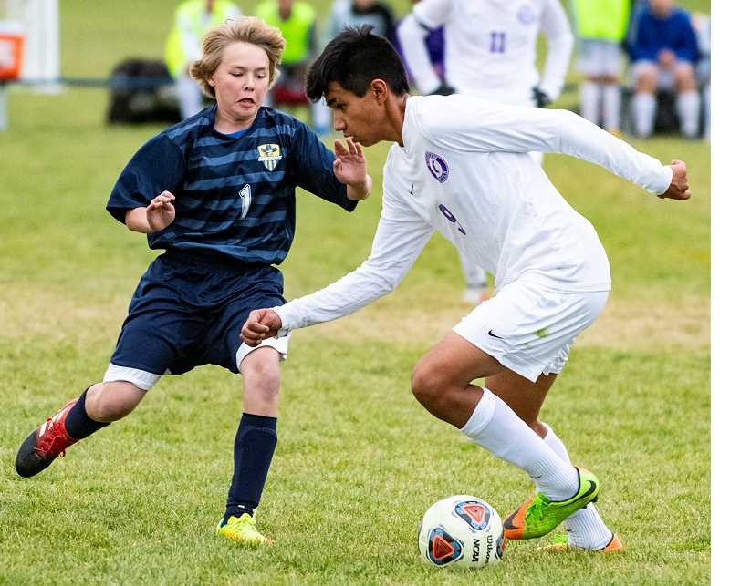 LON AUSTIN/CENTRAL OREGONIAN - Crook County's Mitch Warren challenges Ridgeview's Jonathan Orozco during the Cowboy loss to the Ravens Tuesday night. Orozco scored one goal as Ridgeview took a 5-0 shutout victory, clinching the Intermountain Conference title. Crook County closed out their season with a road match against Redmond on Thursday.