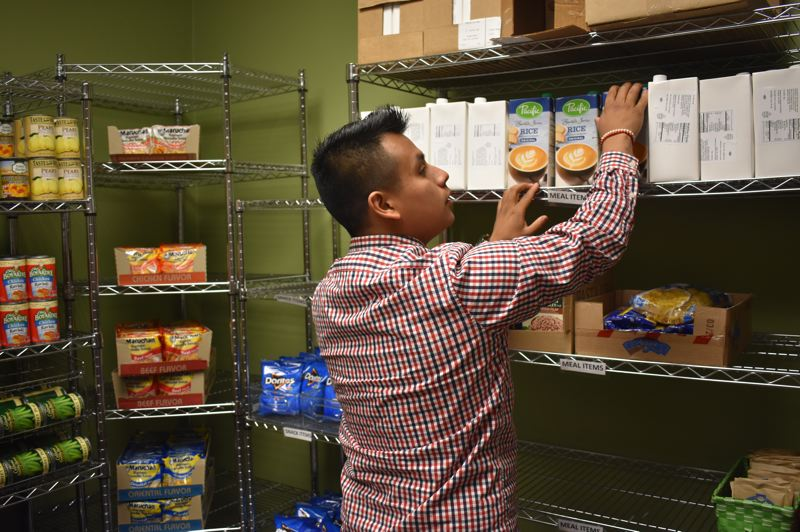 OUTLOOK PHOTO: TERESA CARSON - Kenny Mendoza, leagal affairs representative with the Associated Student Government, tidies up at Barneys Pantry. The MHCC Foundation is supporting the pantry as an increasing number of students are food insecure.