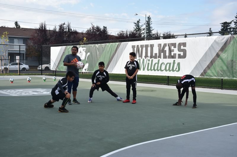 OUTLOOK PHOTO: TERESA CARSON - Some of the visiting Highland Elementary School Huskies stretch before their exhibition game against the Wilkes Wildcats at the opening of the new futsal pitch.