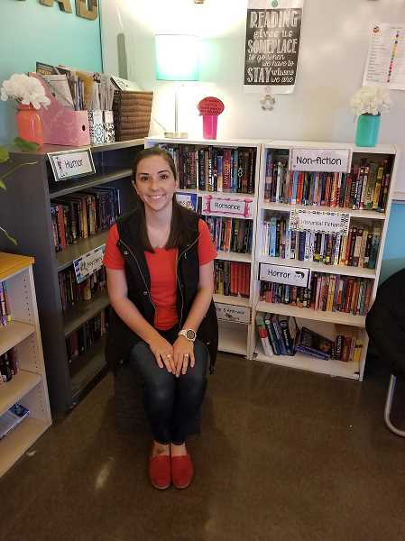 COURTESY PHOTO - Elyse Hansen is pictured with her books. She hopes to expand her library with a $2,500 classroom grant.