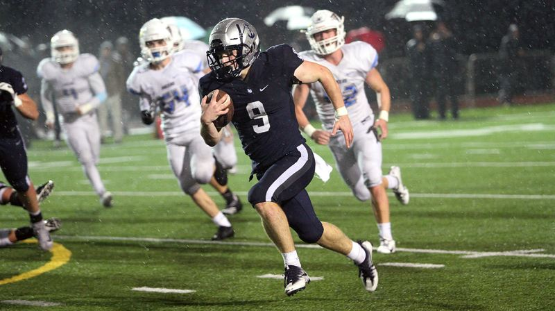 REVIEW PHOTO: MILES VANCE - Lake Oswego junior running back Casey Filkins rushes for some of his 325 yards and four touchdowns during the Lakers' 30-14 win over Lakeridge at Lake Oswego High School on Friday.