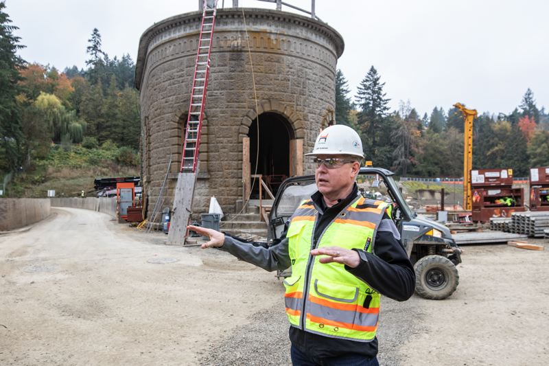 TRIBUNE PHOTO: JONATHAN HOUSE - Cary Bubenik, in front of a cast concrete pump house, talks about improvement happening at the Washington Park reservoirs.