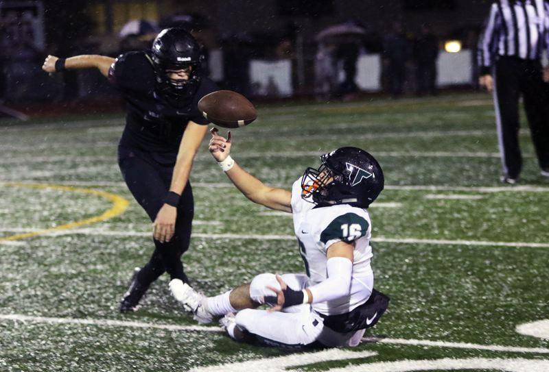 TIMES PHOTO: DAN BROOD - Tigard junior Max Lenzy (right) reaches up to grab the ball, completing a juggling catch in front of Tualatin junior Luke Marion, during the Tigers' 27-14 win over the rival Timberwolves on Friday.