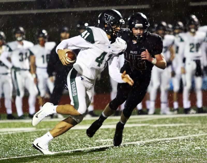 TIMES PHOTO: DAN BROOD - Tigard sophomore quarterback Drew Carter scrambles for yardage during Friday's game at Tualatin.