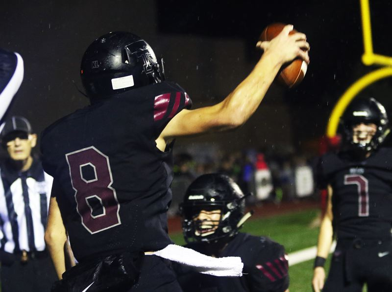 TIMES PHOTO: DAN BROOD - Tualatin junior Cade McCarty holds the ball up after making an interception in the end zone during Friday's game with Tigard.
