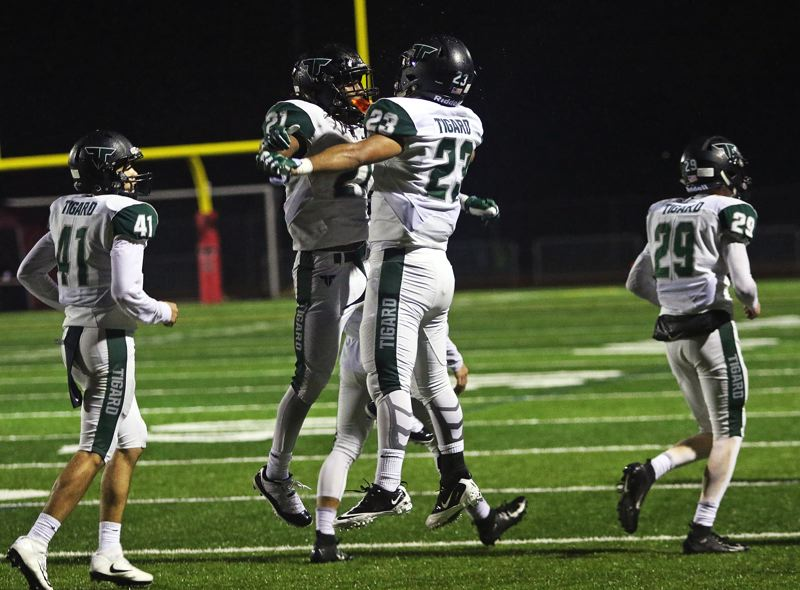 TIMES PHOTO: DAN BROOD - Tigard's Marat Vasilyan (23) and Malcolm Stockdale celebrate after Stockdale's 1-yard touchdown run during Friday's game at Tualatin.