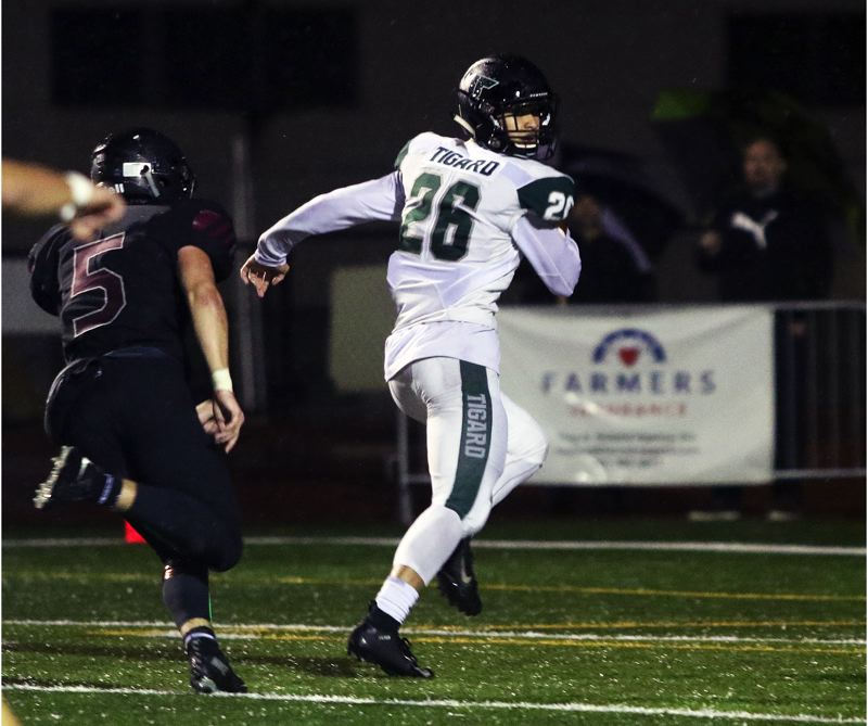 TIMES PHOTO: DAN BROOD - Tigard senior receiver Jazz Ross (26) heads to the end zone to complete a 44-yard touchdown pass play during the Tigers' win at Tualatin.