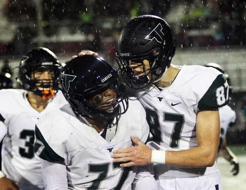 TIMES PHOTO: DAN BROOD - Tigard's Johnny Nomani (77) and Kamryn Hosley are all smiles following the Tigers' 27-14 win at Tualatin on Friday.