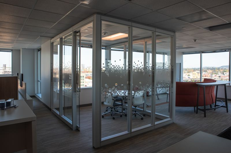 COURTESY: STANTEC - Small rooms enclosed in frosted glass provide private spaces for meetings while also allowing access to natural light.