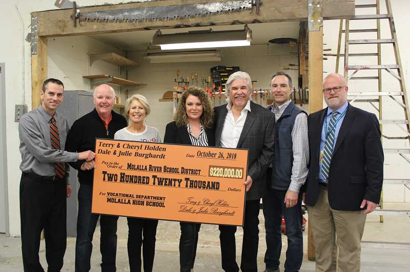 PIONEER PHOTO: KRISTEN WOHLERS - Donors give a check for $220,000 to MHS for career technical education on Friday, Oct. 26. Pictured from left to right are: MHS Principal Brad Berzinski, Terry Holden, Cheryl Holden, Julie Burghardt, Dale Burghardt, manufacturing teacher Craig Simmons and Superintendent Tony Mann.