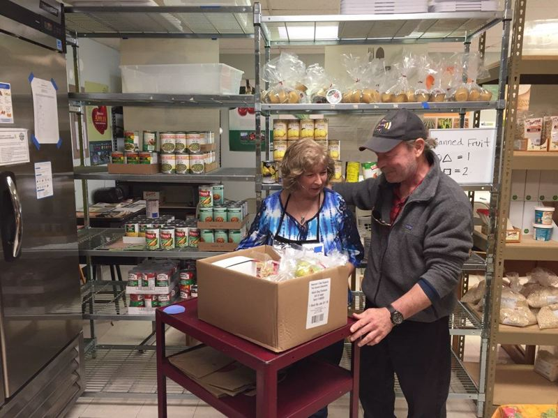 SUBMITTED PHOTO - A volunteer helps a shopper plan nutritious meals at the Gladstone Food Pantry. The facility at Gladstone High School served more than 7,300 people last year.