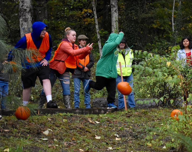 OUTLOOK PHOTO: MATT DEBOW - Attendees at Wood Villages annual Great Pumpkin Fest finish out the event by rolling pumpkins down a hill at the top of Donald Roberston Park.