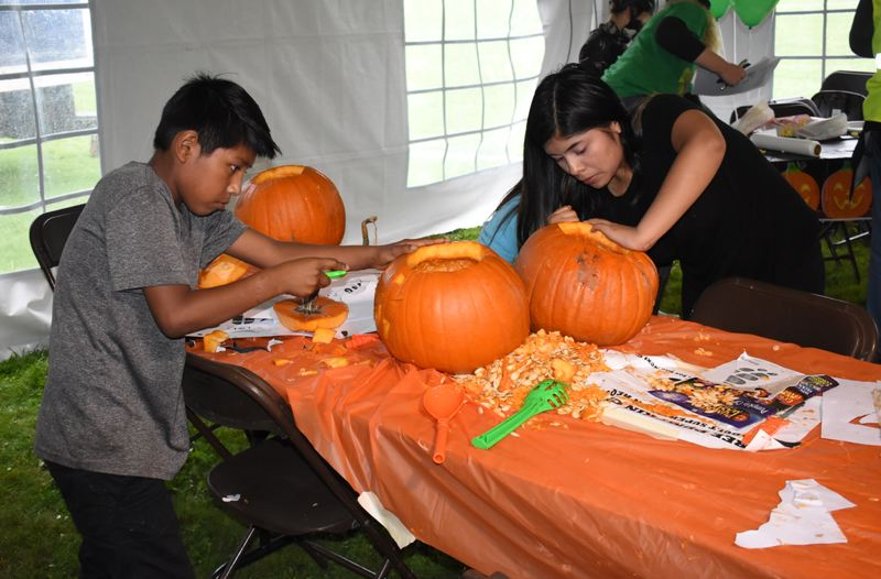 OUTLOOK PHOTO: MATT DEBOW - Brenda Marcelo, 12, and her younger brother Gonzalo, 9, carve pumpkins on Saturday, Oct. 27 at Wood Villages annual Great Pumpkin Festival.