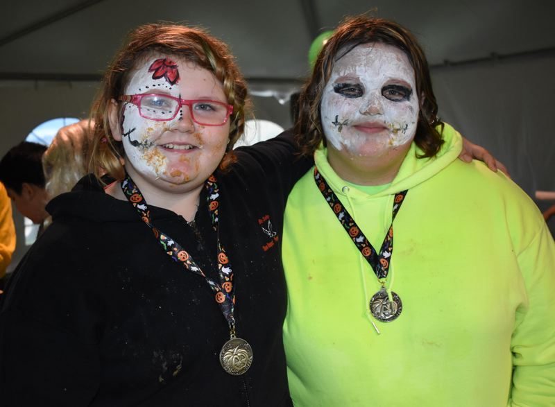 OUTLOOK PHOTO: MATT DEBOW - Sisters Sadie Davis, 13, and Kelsey (left), pose with their medals for winning and second place, respectively, in the pie eating contest during Wood Villages annual Great Pumpkin Festival on Saturday, Oct. 27.