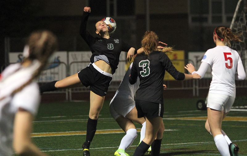 TIDINGS PHOTO: MILES VANCE - West Linn sophomore defender Cami Fulcher makes a header during her team's 7-0 win over Centennial in the first round of the Class 6A state playoffs at West Linn High School on Saturday.