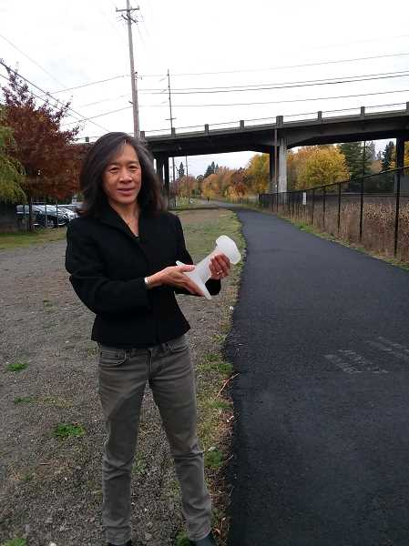 TIMES PHOTO: RAY PITZ - Suenn Ho, a principal with Resolve Architecture and Planning, who is helping design both the Outdoor Museum and Rotary Plaza, holds a glass casting of a partial railroad tie at the entrance to the Tigard Street Heritage Trail and Outdoor Museum planned for downtown Tigard.