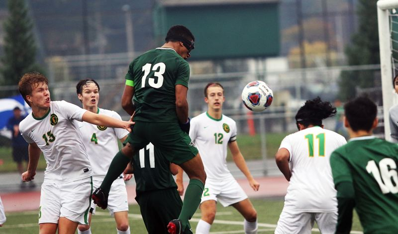 TIMES PHOTO: DAN BROOD - Tigard High School senior Sajjad Al-Rikabi (13) headed in a shot off a corner kick to help the Tigers get a 2-1 win over Cleveland in Saturdays Class 6A state playoff first round match.