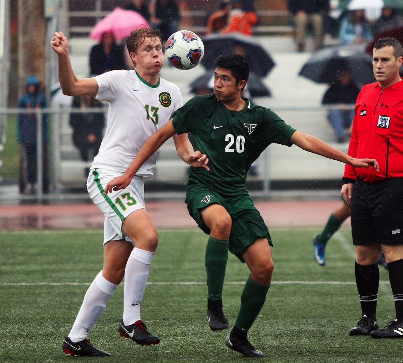 TIMES PHOTO: DAN BROOD - Tigard junior Ivan Orozco (right) battles Cleveland senior Alex Weiler for the ball during Saturdays Class 6A state playoff match.