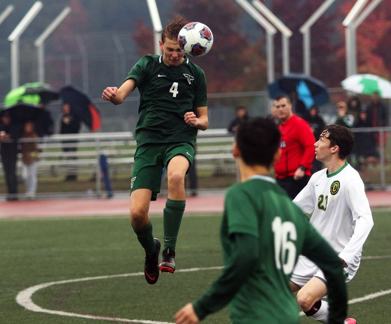 TIMES PHOTO: DAN BROOD - Tigard High School junior defender Jared Debban heads the ball during the Tigers 2-1 playoff win over Cleveland.