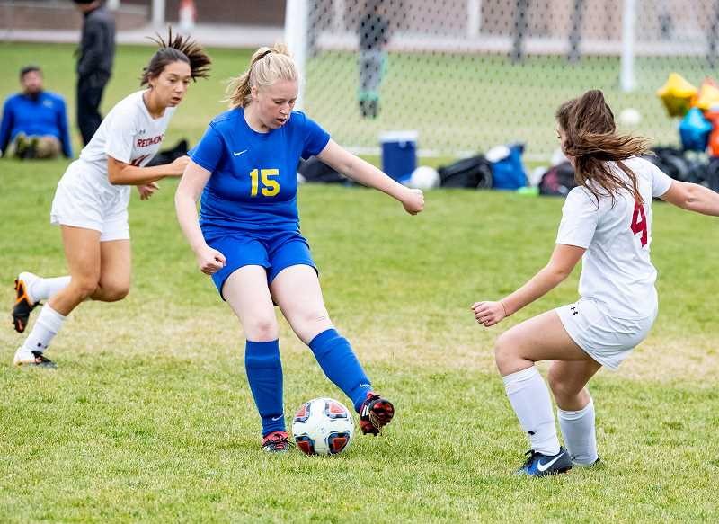 LON AUSTIN/CENTRAL OREGONIAN - Heather Ptomey controls the ball and prepares to play it away from Redmond forward Gracie Murray. Playing at home on senior night, the Cowgirls salvaged a 1-1 tie against the Panthers in the final game of the season for both teams.