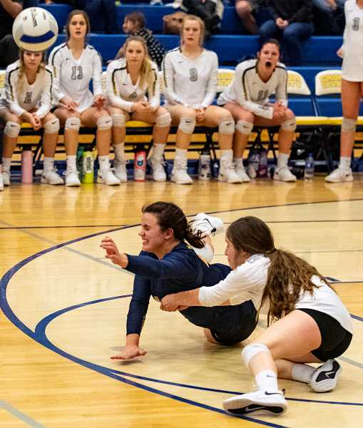 LON AUSTIN/CENTRAL OREGONIAN -  Libero Mekynzie Wells, in blue, dives and pops a ball up in the air for one of her 32 digs, while defensive specialist Stormie Camara covers. Crook County went on to win the point and the match as the Cowgirls edged the North Eugene Highlanders in five sets to earn a berth in the state tournament.