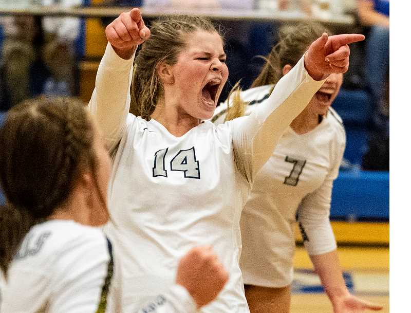 LON AUSTIN/CENTRAL OREGONIAN - Kenna Woodward, center, and Lily Cooper, right, celebrate as the Cowgirls win the fifth and deciding set of their Saturday night match with North Eugene. With the win the Cowgirls advance to the state tournament where they will take on West Albany on Friday.