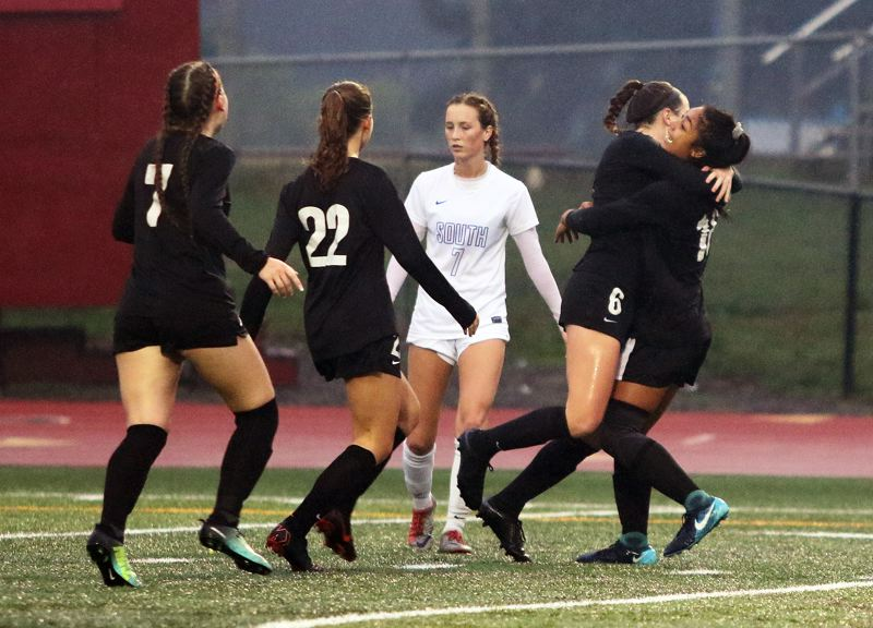 TIMES PHOTO: DAN BROOD - Tualatin High School senior Meghan MacPherson (second from right) is congratulated by her teammates Cally Togiai (far right), Skylar Maddox (7) and Brook Burke after scoring against South Medford.