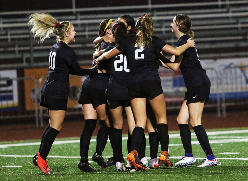 TIMES PHOTO: DAN BROOD - Members of the Sherwood High School girls soccer team celebrate with junior Loma McNeese following her go-ahead free-kick goal in the Lady Bowmens 3-2 playoff win over South Eugene.