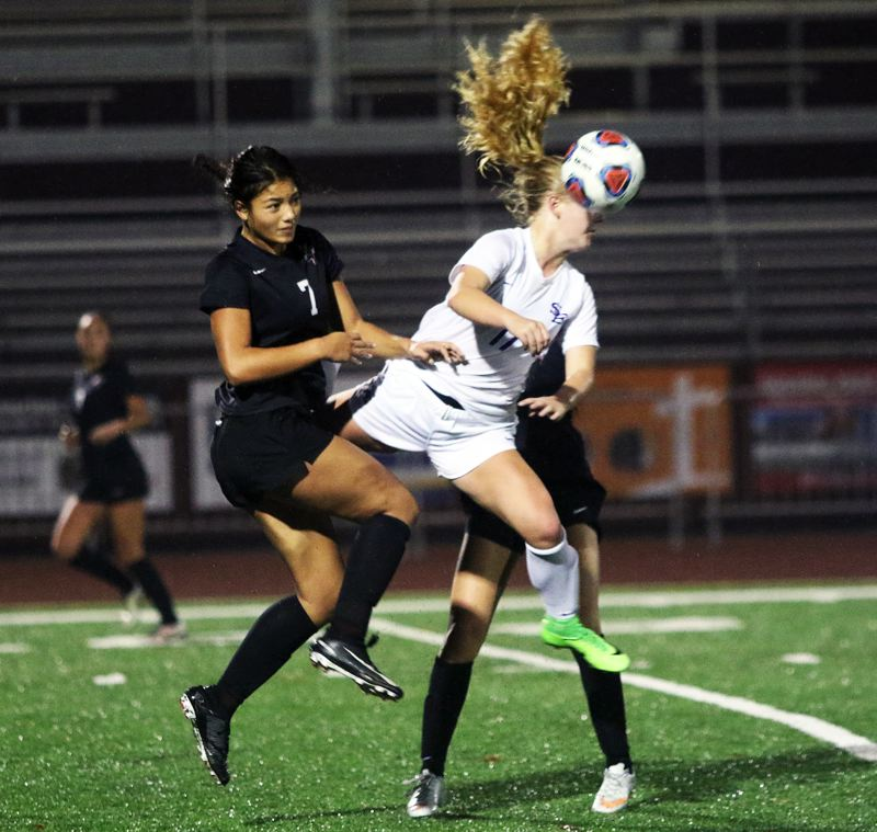 TIMES PHOTO: DAN BROOD - Sherwood High School junior Loma McNeese (left) and South Eugene sophomore Lily Lauderbach go up for the ball during Saturdays state playoff match.