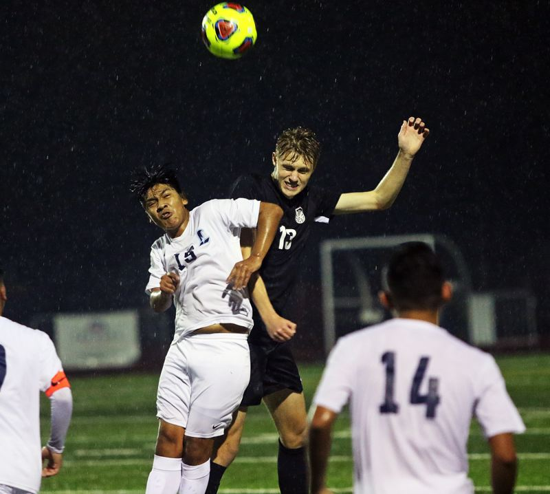 TIMES PHOTO: DAN BROOD - Tualatin senior Thomas Augee (right) and Liberty junior Marcos Salinas Orozco go up for the ball during Saturdays state playoff match.