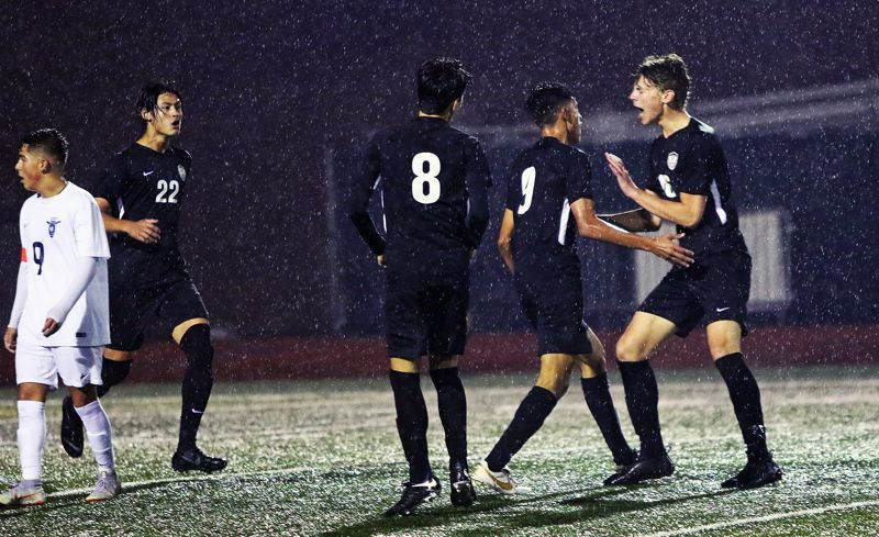 TIMES PHOTO: DAN BROOD - Tualatin senior Mario Quiterio (9) is congratulated by teammates (from left) Christian Pumpelly, Santiago De La Torre and Zach Wesson after scoring against Liberty.