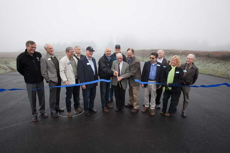 TIMES PHOTO: JAIME VALDEZ - Washington County Commissioner Roy Rogers cuts the ribbon marking the substantial completion of the 124th Avenue extention Tuesday, aided by Tualatin Mayor Lou Ogden, left, and Washington County Commission Chairman Andy Duyck.