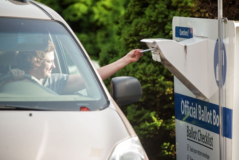 FILE PHOTO - A voter drops off a ballot at a drive-by drop site in Portland in 2016.