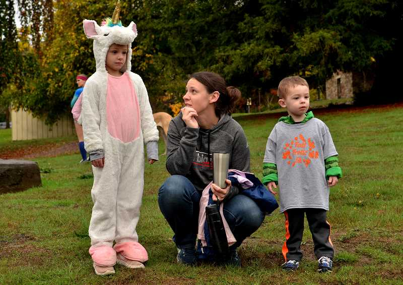 From left, Alison, Nicole and Nolan Robinson watch as runners finish the kids dash.