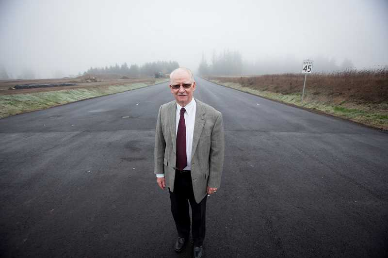 TIMES PHOTO: JAIME VALDEZ - Washington County Commission Chairman Roy Rogers stands in the middle of the newly dedicated 124th Avenue extension Monday morning. Rogers said he won't be around in 35 years to see what the fate of the roadway will be but thanked all those who made it possible. While a county road, property on the right side of Rogers will be developed by Sherwood for light industrial use. On the other side of the road, the city of Tualatin will have the same designation for the property it owns.