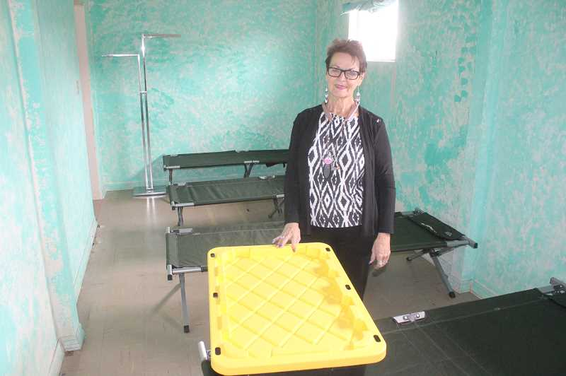 SUSAN MATHENY/MADRAS PIONEER - Pat Abernathy stands in the men's sleeping room, showing one of the plastic totes they will be given to store their things.