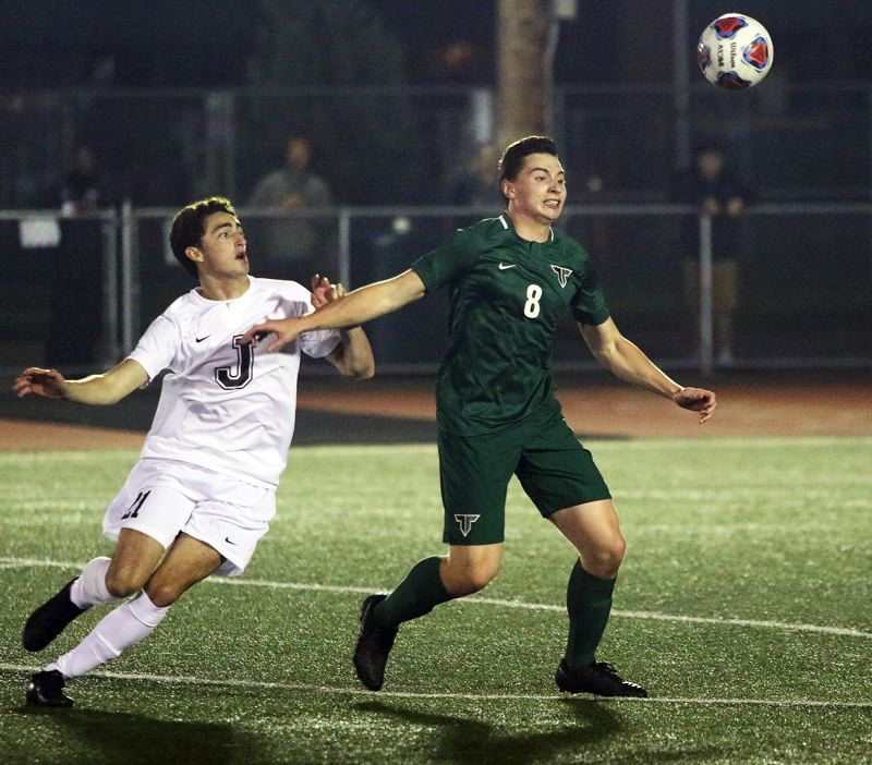 TIMES PHOTO: DAN BROOD - Jesuit junior Remington Grayson (left) and Tigard senior Carson Mandera battle for the ball during Tuesdays state playoff contest.