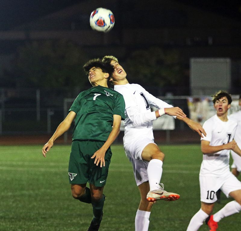 TIMES PHOTO: DAN BROOD - Tigard High School junior Rasheed Tahuni (7) goes up for a header during the Tigers state playoff match with Jesuit on Tuesday.