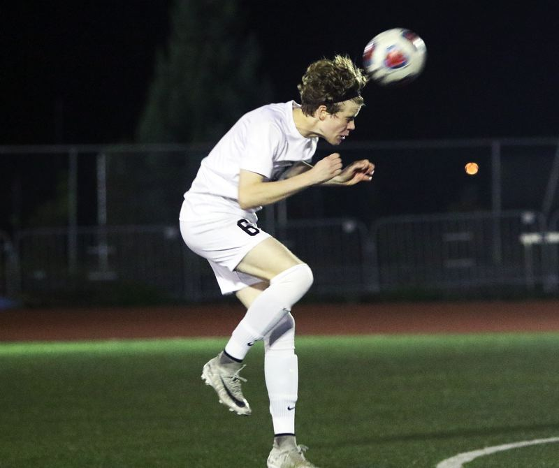 TIMES PHOTO: DAN BROOD - Jesuit senior Ben Landauer heads the ball during Tuesday's state playoff match at Tigard.