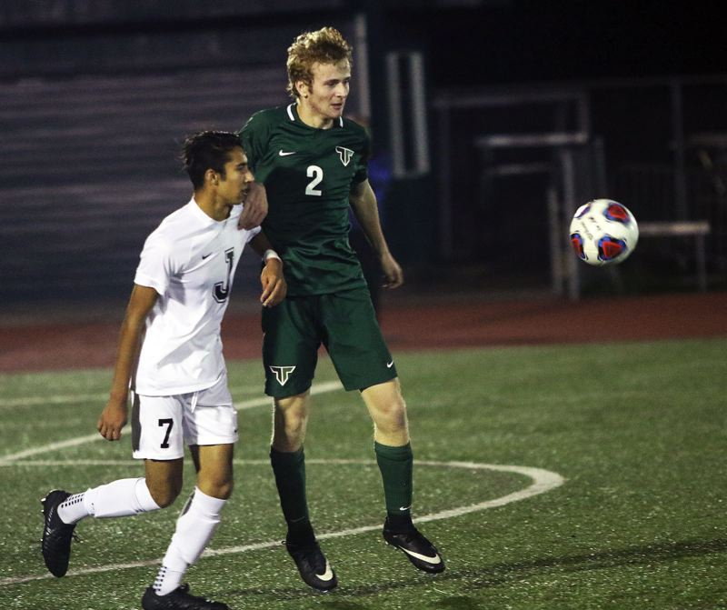 TIMES PHOTO: DAN BROOD - Jesuit sophomore Aidan Azavedo (left) and Tigard sophomore Jack Hallam eye the ball during Tuesday's state playoff match.