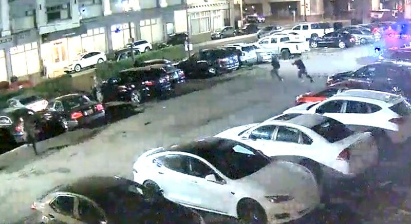 COURTESY PHOTO: PORTLAND POLICE BUREAU - A Portland police officer and a sergeant, right in middle of parking lot, run toward a man with a gun during a Sept. 30 shooting near Southwest Third Avenue and Harvey Milk Street captured on video from nearby cameras. Patrick Kimmons was killed in the incident.