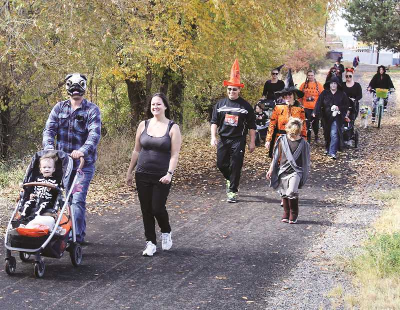 JASON CHANEY/CENTRAL OREGONIAN - Costumed runners and walkers participate in the first-ever Halloween Hustle 5K, a Rotary Club of Crook County-led fundraiser held on Saturday afternoon.