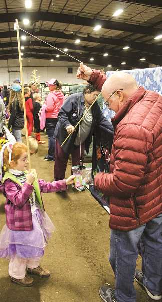 JASON CHANEY/CENTRAL OREGONIAN - Kieran Sutherlin wins a prize at a fishing booth at the annual Harvest Party, hosted this year at the Crook County Fairgrounds by High Desert Christian Academy.