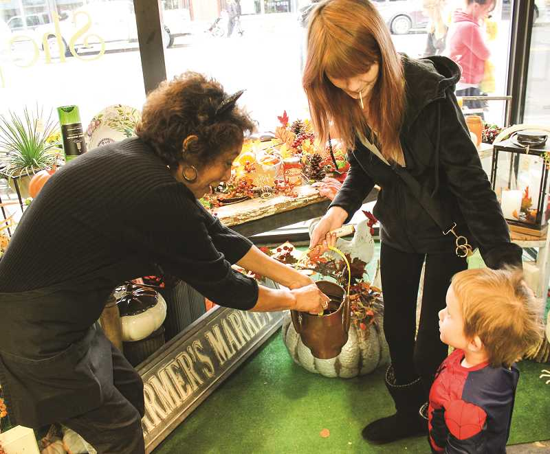 JASON CHANEY/CENTRAL OREGONIAN - Rosemary Harris hands out goodies to Maddex Stafford and Krista McDaniel at The Posie Shoppe, one of many stops on the Chamber of Commerce-hosted Candy Crawl.