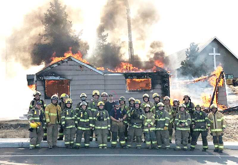SUBMITTED PHOTO - More than two dozen volunteers, along with two staff firefighters for the Jefferson County Fire District, pose beside a house being used as a 'burn to learn' building. The firefighters practiced their skills on the house, which belongs to the Madras Free Methodist Church, for several hours on Saturday, Oct. 27, before finally letting it go up in flames. The church plans to extend its parking in that area.