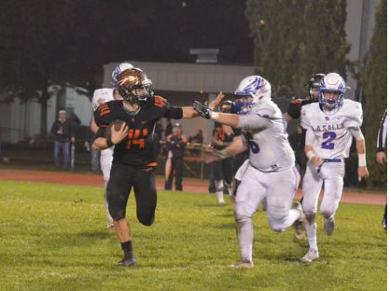 PHOTO COURTESY: JOHN BREWINGTON - Connor McNabb (left) of Scappoose starts a long run with a stiff-arm during last week's league playoff victory over La Salle Prep. The Indians are back at home this Friday, facing North Bend in the Class 5A playoffs.