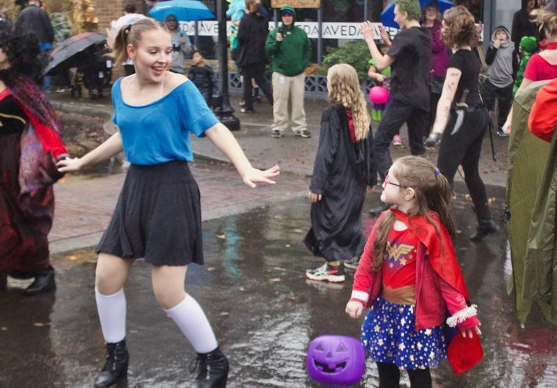 OUTLOOK PHOTO: CHRISTOPHER KEIZUR - Peyton Marleau danced with a young trick-or-treater during a performance by Greshams SALT Academy.