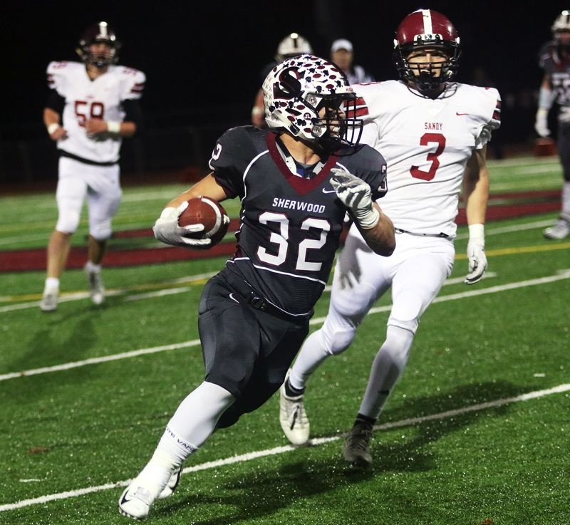 TIMES PHOTO: DAN BROOD - Sherwood senior running back Ian Stormont heads up field, ahead of Sandy junior Colby Carson, after catching a swing pass during Friday's playoff game.